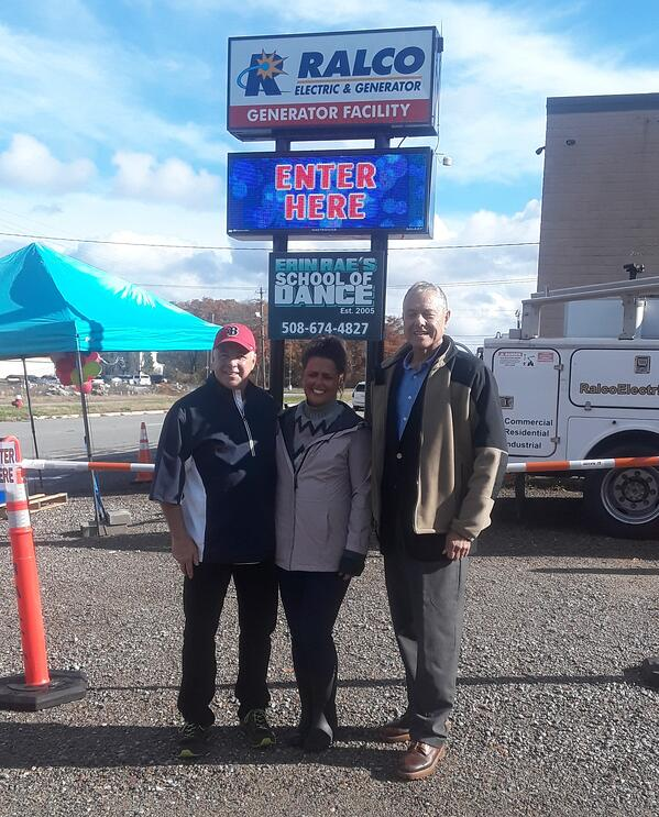 family in front of RALCO sign during food drive